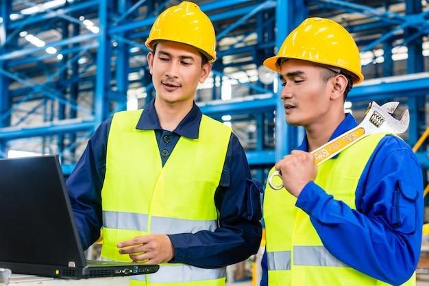 Werknemer in aziatische productie-installatie met laptop bespreken