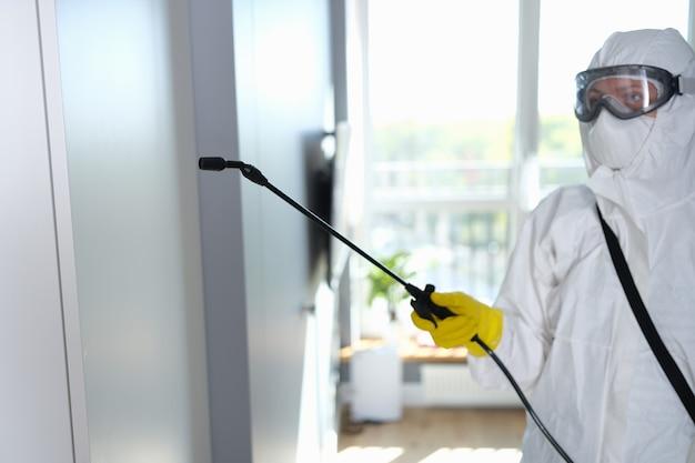 Werknemer in beschermend pak, masker en bril desinfecteert pand closrup