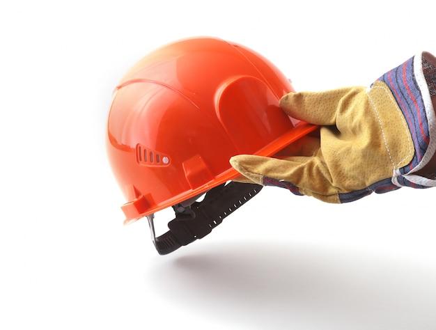 Werknemer in beschermende handschoenen heeft een oranje helm in zijn hand.