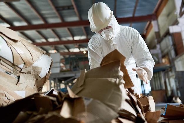 Werknemer in beschermende pak sorteren karton