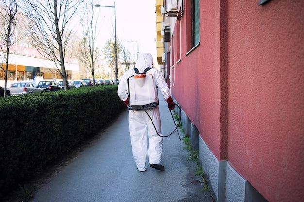 Werknemer in chemisch beschermingspak die desinfectiemiddel op openbare oppervlakken sproeit