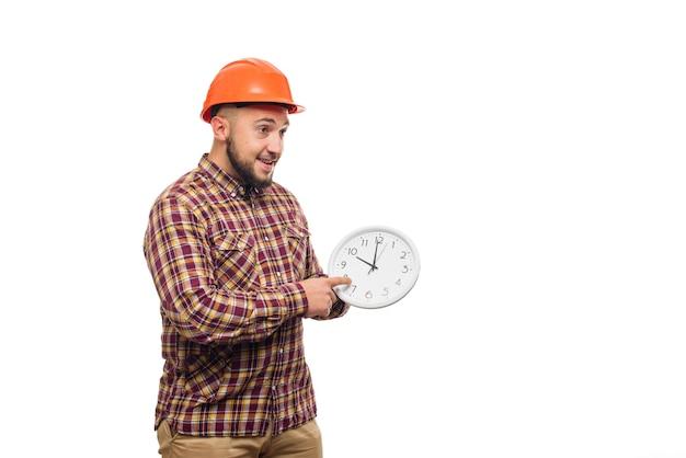 Werknemer in de beschermende wekker van de helmholding op wit. tijd om te werken. bouwtijd