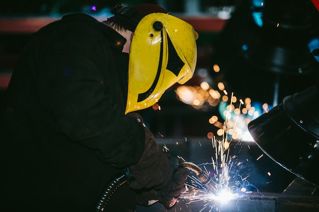 Werknemer in de fabriek in de helm is van ijzer in het lasproces heldere vonken
