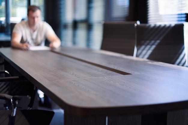 Werknemer in de vergaderruimte van het kantoor. manager aan tafel in moderne vergaderruimte voor zakelijke onderhandelingen en zakelijke bijeenkomsten. interview met een nieuwe medewerker.