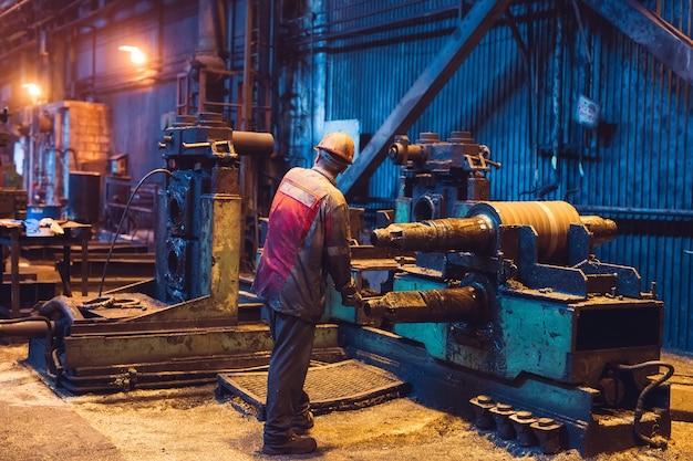 Werknemer in de zware industrie werkt hard op de machine. ruwe industriële omgeving.
