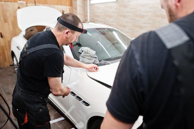 Werknemer in detaillering garage zet polyurethaan anti-grind film hoes in witte luxe auto.