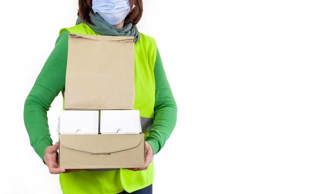 Werknemer in een groen vest met veel kartonnen dozen, leveringsconcept.