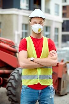 Werknemer in een veiligheidsvest staande bij een gebouwde constructie