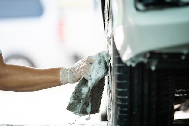 Werknemer in garage die een vuile auto wast met behulp van een autowasmachine-zeep en een borstel om vuil van een band te wassen