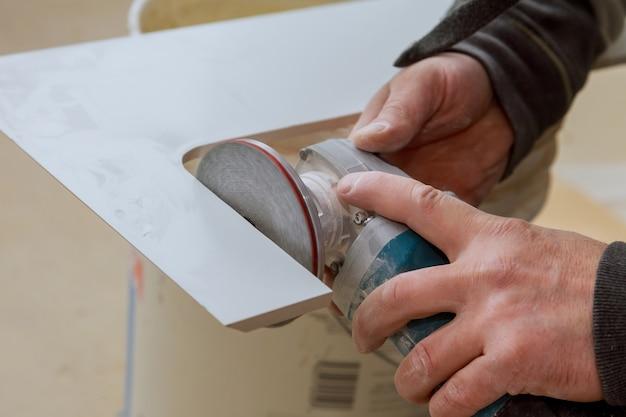 Werknemer in gebruik molen voor het snijden van tegels porselein steengoed werk