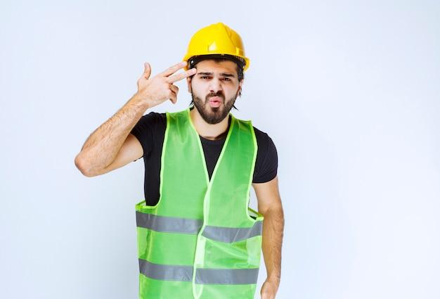 Werknemer in gele helm denken en ziet er verward uit.