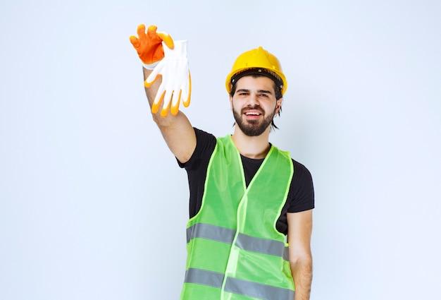 Werknemer in gele helm die zijn werkplaatshandschoenen uithaalt en demonstreert.