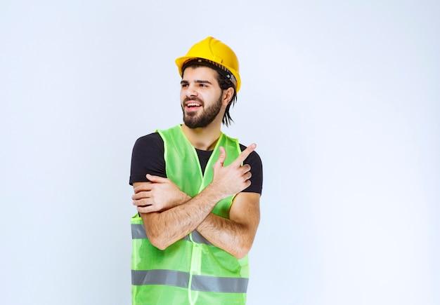 Werknemer in gele helm en groene jas die naar boven wijst.