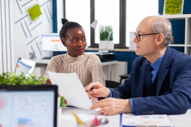 Werknemer in gesprek met senior executive op zoek naar financiële grafieken in de vergaderruimte van het opstartende bedrijf