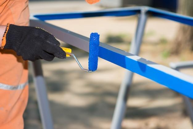 Werknemer in handschoenen met een roller schildert metaalblauw