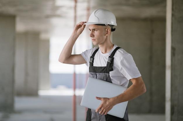 Werknemer in harde hoed die op laptop werkt