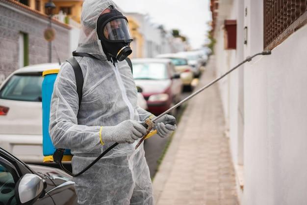 Werknemer in hazmat pak dragen gasmasker bescherming tijdens het desinfecteren in de straat van de stad