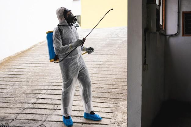 Werknemer in hazmat pak dragen van gezichtsmasker bescherming tijdens het desinfecteren in de stad gebouw