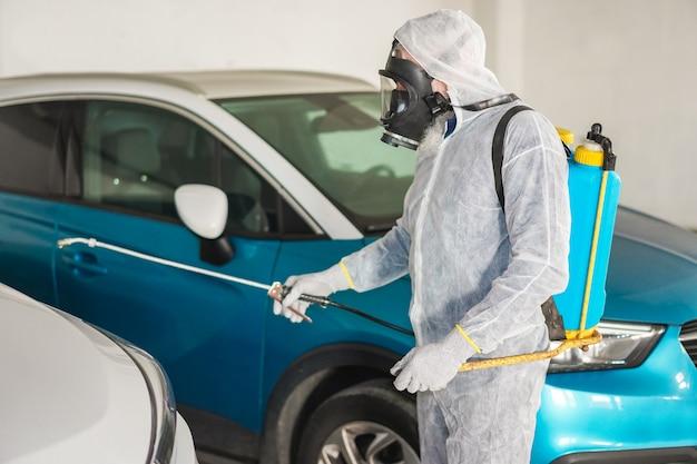 Werknemer in hazmat pak met gasmasker bescherming tijdens het desinfecteren in de straat