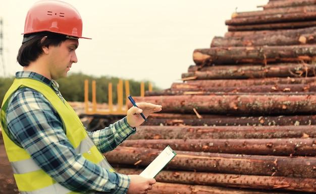 Werknemer in helm telt hout timmerhout