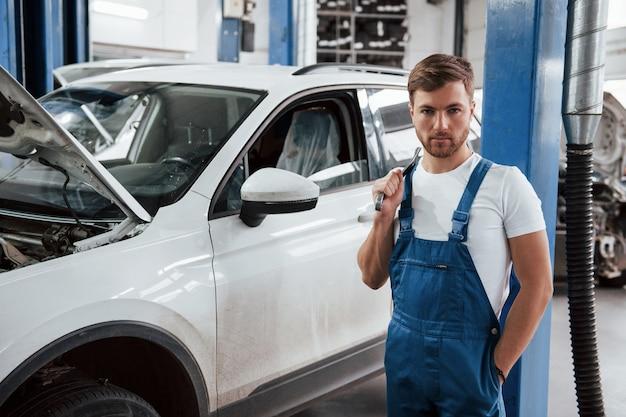Werknemer in het blauw gekleurde uniform werkt in de autosalon.