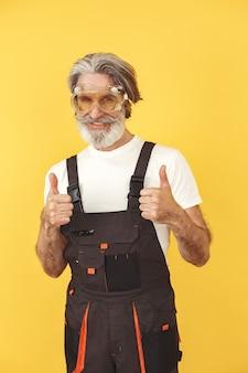 Werknemer in overall. man met gereedschap. oudste in gele glazen.