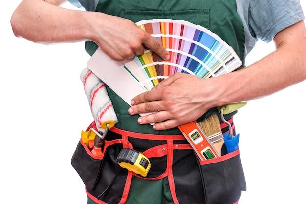 Werknemer in overall wijzend op kleurstaal