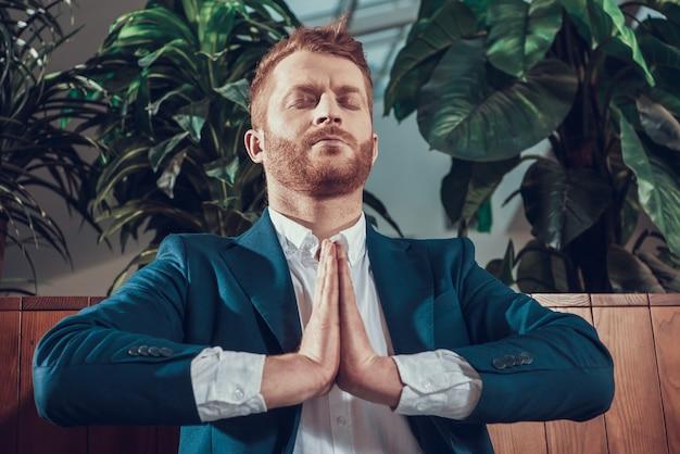 Werknemer in pak mediteren op bankje in kantoor.
