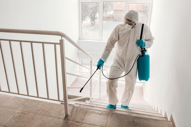 Werknemer in steriel uniform, met handschoenen en gezichtsmasker steriliserende reling op school.