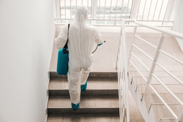 Werknemer in steriel uniform, met handschoenen en gezichtsmasker steriliserende trappen op school.