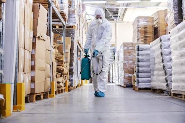 Werknemer in steriel uniform met rubberen handschoenen met sproeier met desinfectiemiddel