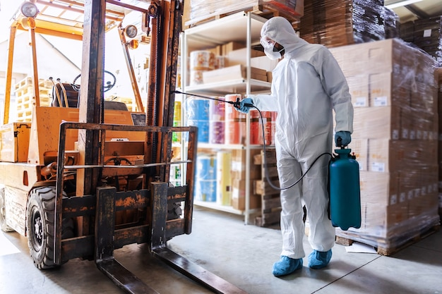 Werknemer in steriel uniform met rubberen handschoenen met sproeier
