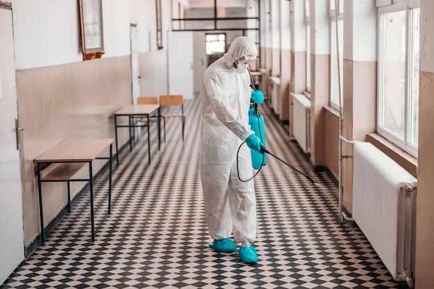 Werknemer in steriel wit uniform, met masker en bril met sproeier met ontsmettingsmiddel en sproeien rond gang op school