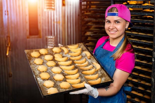 Werknemer in steriele doeken en witte rubberen handschoenen met versgebakken koekjes. voedselproductie fabriek.