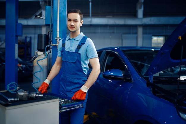 Werknemer in uniform bij de gereedschapskist, autoservicestation. automobielcontrole en inspectie, professionele diagnostiek en reparatie
