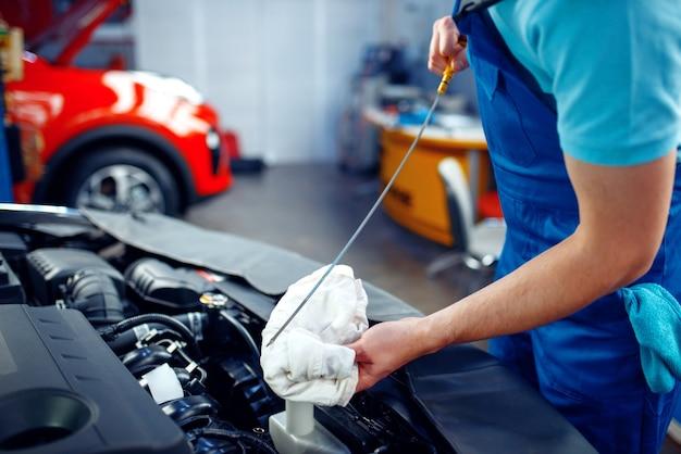 Werknemer in uniform controleert het motoroliepeil, autoservicestation. automobielcontrole en inspectie, professionele diagnostiek en reparatie