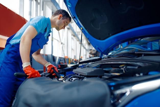 Werknemer in uniform controleert motor, autoservice