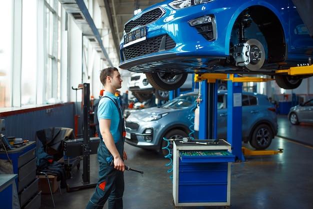 Werknemer in uniform controleert voertuigbodem op lift, autoservicestation. automobielcontrole en inspectie, professionele diagnostiek en reparatie