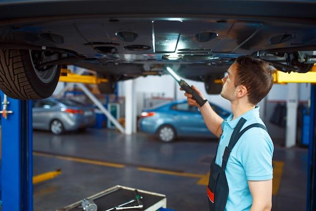 Werknemer in uniform controleert voertuigophanging op lift, auto servicestation. automobielcontrole en inspectie, professionele diagnostiek en reparatie