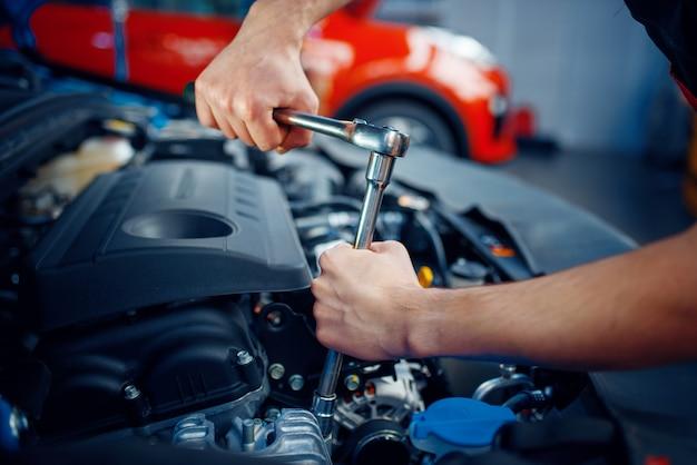 Werknemer in uniform demonteert de motor van het voertuig, auto-servicestation. automobielcontrole en inspectie, professionele diagnostiek en reparatie