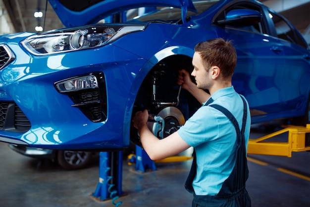 Werknemer in uniform fix probleem op voertuig met verwijderd wiel, autoservicestation. automobielcontrole en inspectie, professionele diagnostiek en reparatie