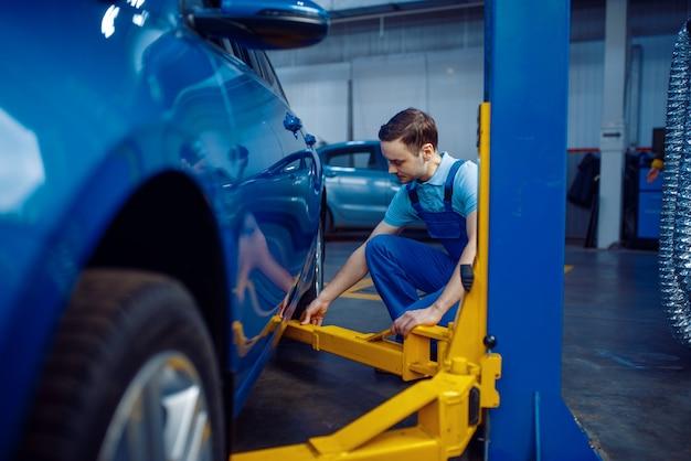 Werknemer in uniform fix voertuig op lift, autoservice