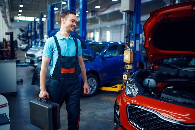 Werknemer in uniform houdt een gereedschapskist, auto-servicestation. automobielcontrole en inspectie, professionele diagnostiek en reparatie