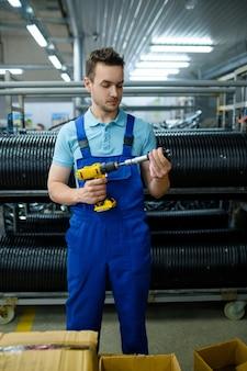 Werknemer in uniform houdt elektrische schroevendraaier en fietsnaaf, rijen banden. montage van fietswielen op fabriek, installatie van fietsonderdelen