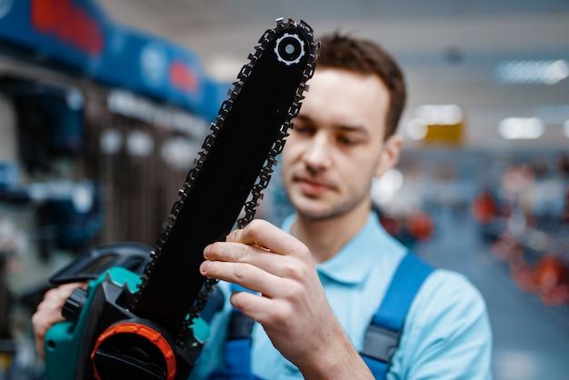 Werknemer in uniform houdt elektrische zaag in gereedschapsopslag