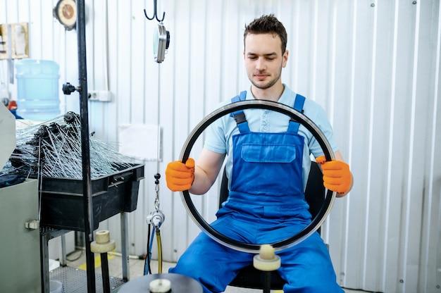 Werknemer in uniform houdt nieuwe aluminium fietsvelg op fabriek. montage van fietswielen in de werkplaats, installatie van fietsonderdelen