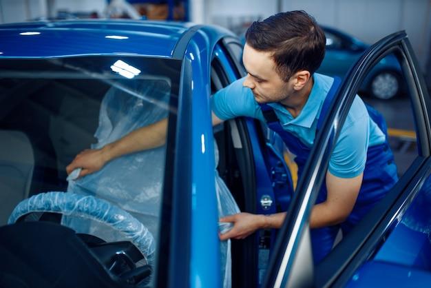 Werknemer in uniform legt de stoelbekleding, autoservicestation. automobielcontrole en inspectie, professionele diagnostiek en reparatie