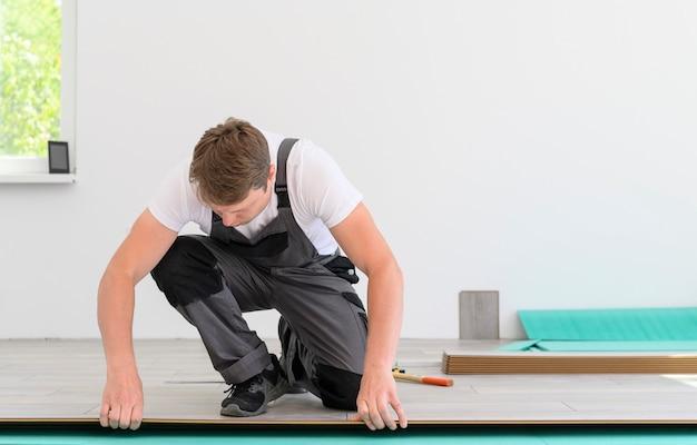Werknemer in uniform legt het laminaat in witte kamer witte kamer achtergrond met kopieerruimte voor ad