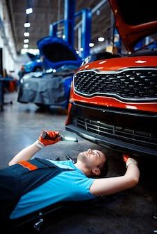 Werknemer in uniform liggend onder het voertuig, autoservicestation. automobielcontrole en inspectie, professionele diagnostiek en reparatie