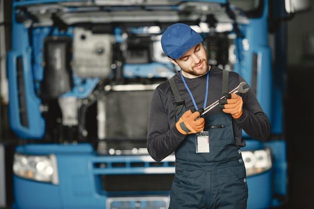 Werknemer in uniform. man repareert een vrachtwagen. man met gereedschap